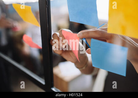 Close up shot of hands of woman sticking adhesive notes on glass wall in office - Stock Photo