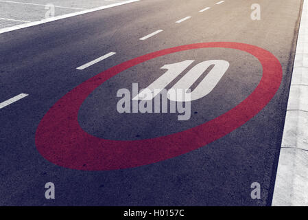 10 kmph or mph driving speed limit sign on highway, road safety and preventing traffic accident concept. - Stock Photo