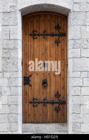 thick ornate old door with ironwork in sandstone wall of old building in belgian town of Ghent - Stock Photo