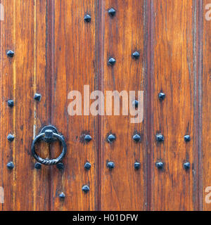 part of thick very old wooden door of church or medieval building with cast iron handle - Stock Photo