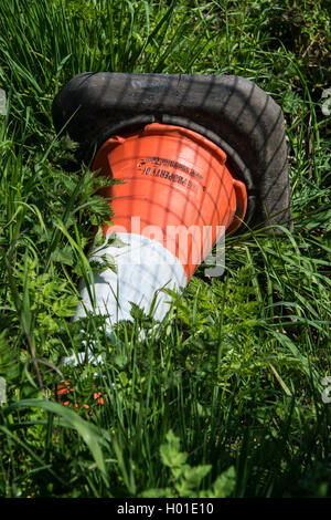 Abandoned traffic cone on a grass verge - Stock Photo