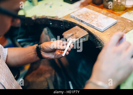 Goldsmith crafting jewels the traditional way - Stock Photo