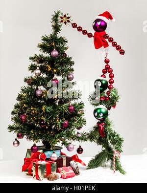 Christmas characters decorating  Christmas tree, hanging star. - Stock Photo