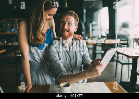 Woman and man flirting in cafe while discussing tablet content - Stock Photo