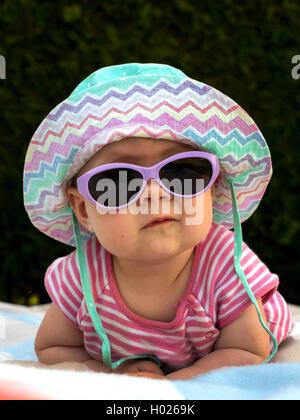 Baby mit Sonnenhut und Sonnenbrille in der Sommerhitze, Oesterreich   baby with sun hat and sun glasses in the summer - Stock Photo