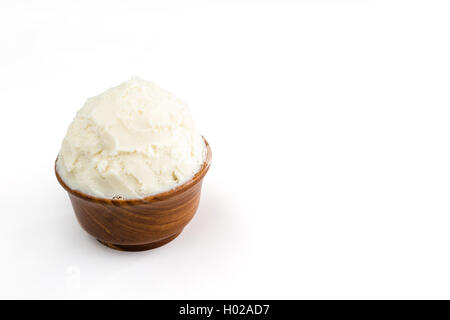 Unrefined, organic Shea butter in the wooden bowl standing on the clean white background. - Stock Photo