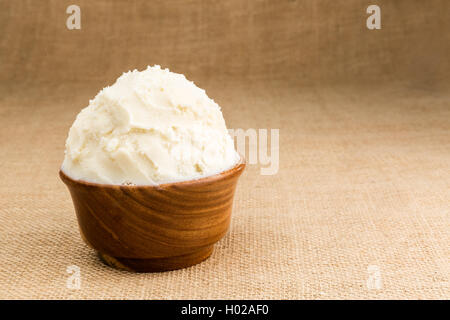 Unrefined, organic Shea butter in the wooden bowl stands on the jute fabric background. - Stock Photo