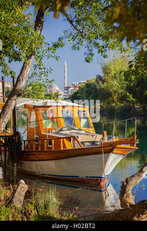 Image of a boat by the river-bank in Manavgat, Turkey. Manavgat mosque in the background. - Stock Photo