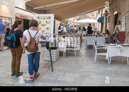 DUBROVNIK, CROATIA - MAY 28, 2014: Tourists looking at menu in front of the restaurant terrace. Dubrovnik has many - Stock Photo