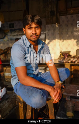 MUMBAI, INDIA - 08 JANUARY 2015: Worker on a fishmarket next to Dhobi ghat posing while waiting for customers. - Stock Photo