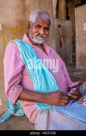 HAMPI, INDIA - 28 JANUARY 2015: Indian man with harelip relaxing in temple with newspapers - Stock Photo