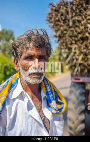 HAMPI, INDIA - 28 JANUARY 2015: Portrait of Indian worker next to truck loaded with sugarcane - Stock Photo