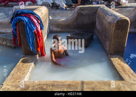 MUMBAI, INDIA - 10 JANUARY 2015: Indian child bathes in traditional laundromat pool in Dhobi Ghat. A well known - Stock Photo