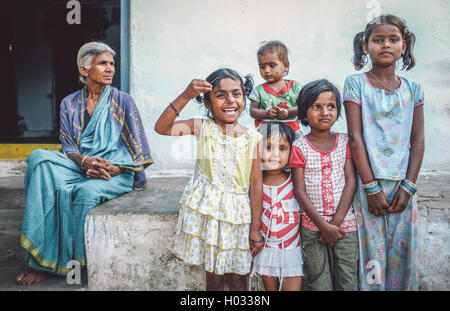 HAMPI, INDIA - 31 JANUARY 2015: Indian family members standing in front of house. Grandmother overlooks five granddaughters. - Stock Photo