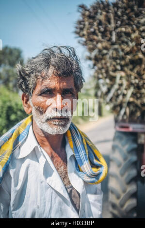 HAMPI, INDIA - 28 JANUARY 2015: Portrait of Indian worker next to truck loaded with sugarcane. Post-processed with - Stock Photo