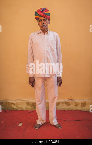 GODWAR REGION, INDIA - 15 FEBRUARY 2015: Elderly Indian man poses in-front of blank wall on red carpet wearing white - Stock Photo