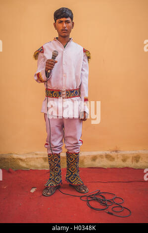GODWAR REGION, INDIA - 15 FEBRUARY 2015: Young Indian musician dressed in wedding ceremony outfit holds microphone. - Stock Photo