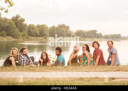 8 young good looking adults laying on grass close to lake in summerly feel - Stock Photo