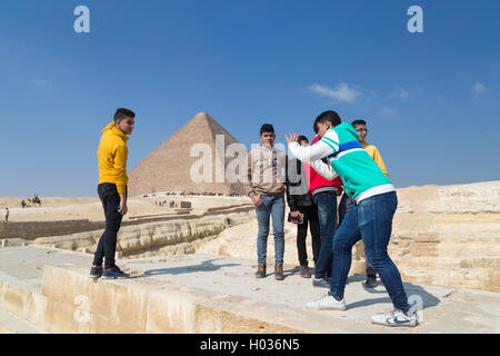 CAIRO, EGYPT - FEBRUARY 1, 2016: Group of local boys taking photos in front of the Great pyramid of Giza. - Stock Photo