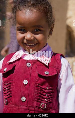 ASWAN, EGYPT - FEBRUARY 7, 2016: Portrait of cute local girl on street of Nubian village on the Nile. - Stock Photo