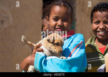ASWAN, EGYPT - FEBRUARY 7, 2016: Local girl holding puppy in Nubian village on the Nile posing for camera. - Stock Photo