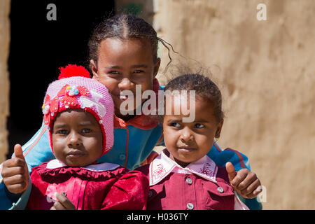 ASWAN, EGYPT - FEBRUARY 7, 2016: Local girls posing in front of the house in Nubian village on the Nile. - Stock Photo