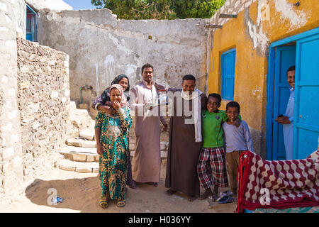 ASWAN, EGYPT - FEBRUARY 7, 2016: Local family posing in front of the house in Nubian village on the Nile. - Stock Photo
