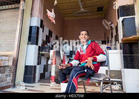 DARAW, EGYPT - FEBRUARY 6, 2016: Young local butcher sitting on the chair holding knife in front of butcher shop. - Stock Photo