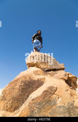 ASWAN, EGYPT - FEBRUARY 7, 2016: Local tourist standing on big rock in desert, Egypt. - Stock Photo