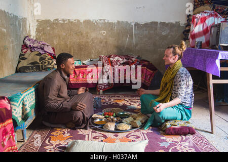 ASWAN, EGYPT - FEBRUARY 7, 2016: Local man and tourist having traditional Egyptian / Nubian lunch. - Stock Photo