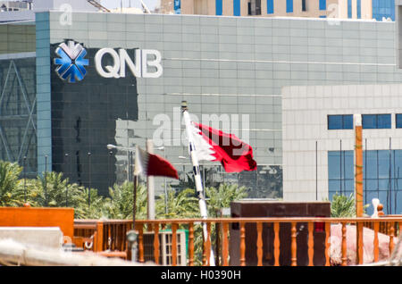 Qatar National Bank (QNB) office in Doha, with qatari flags - Stock Photo