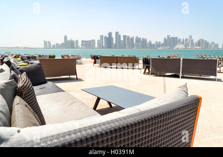Empty restaurant and snack tables and chairs in Doha, with a view of the West Bay financial district - Stock Photo