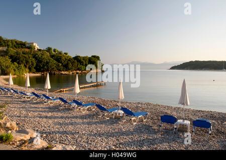 Beach chairs at sunrise on Avlaki beach in northeast Corfu, The Ionian Islands, The Greek Islands, Greece, Europe - Stock Photo