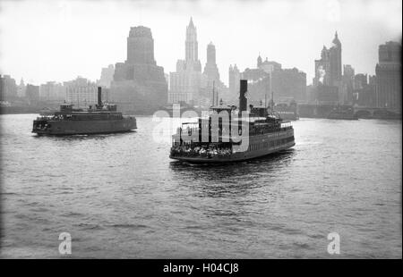 Steam ferry ships crossing the Hudson River towards Lower Manhattan in New York USA 1930s - Stock Photo