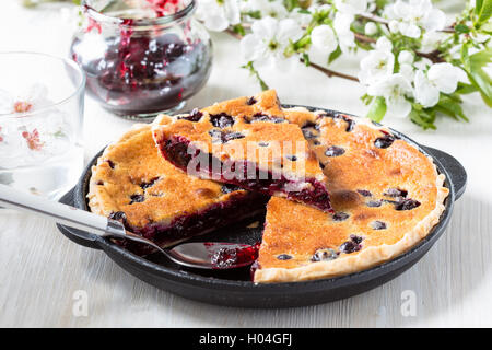 Homemade berry custard tart in frying pan on rustic background spring blossom, eco food, concept - Stock Photo