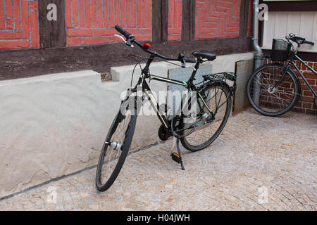 City Bicycle leaning against a house wall. - Stock Photo