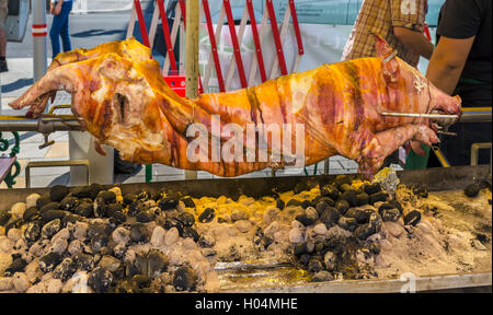 Whole pig roasting on a spit in the Naschmarkt, Linke Wienseile, Vienna, Austria - Stock Photo