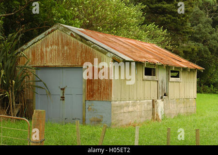 Shed made of rusty corrugated sheet metal on concrete base - Stock Photo