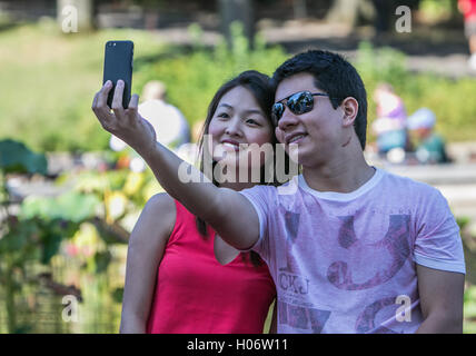 A young couple is taking a selfie in Central Park. - Stock Photo