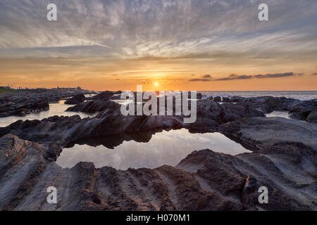 Sunrise light hitting sea rocks by the beach in the morning in Minamiboso, Chiba Prefecture, Japan - Stock Photo