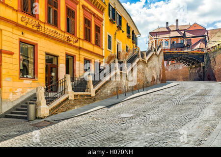 Cobblestone street passes under The Bridge of Lies, a landmark of the old town of Sibiu, Romania - Stock Photo