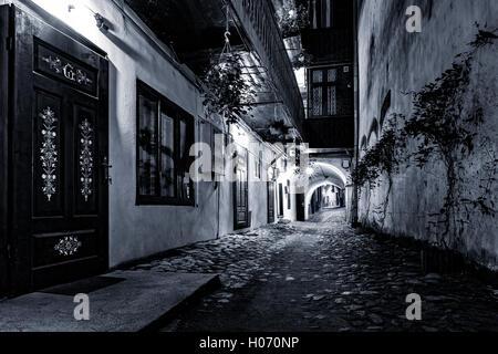 Moody monochrome view of a cobblestone street passage in the old city center of Sibiu, Romania - Stock Photo