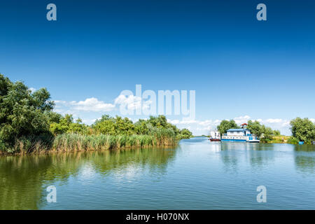 Typical Danube Delta landscape with lakes, canals and lush vegetation on a clear sunny day, in Gura Portitei resort, - Stock Photo