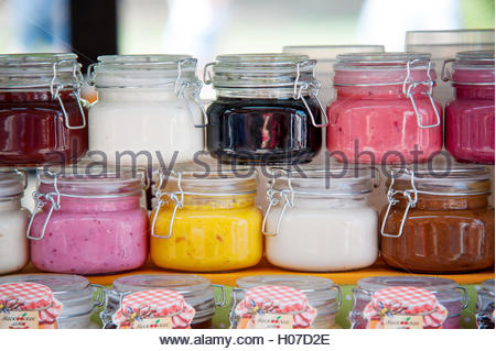 Two rows of the glass jars with pink, white, red, brown and yellow jams and honey. - Stock Photo