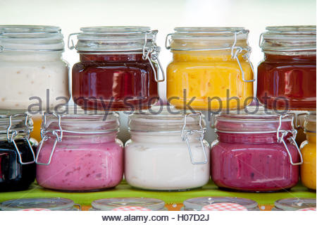 Two rows of the glass jars with pink, white, red and yellow jams and honey. - Stock Photo