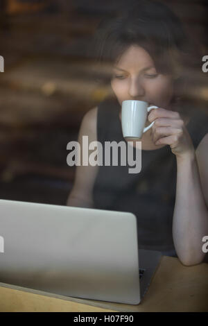 portrait of beautiful young woman sitting in modern cafe holding cup h07f90