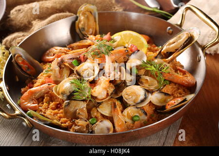 Pan of fried rice with clams, oysters and shrimps - Stock Photo
