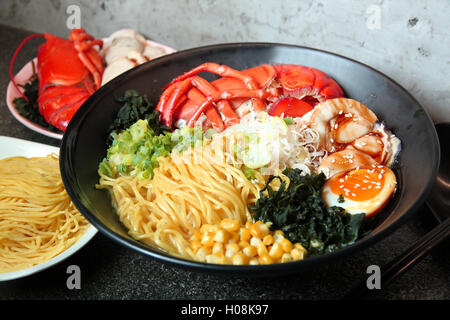 Traditional chinese bowl of wanton and vermicelli with shrimp, egg, corn and herbs on the table in restaurant - Stock Photo