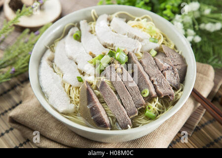 Chinese bowl of wanton noodle with beef anf pork on the table in restaurant - Stock Photo