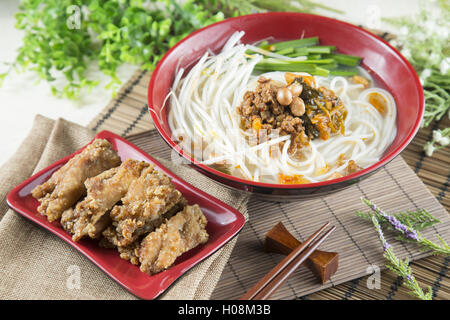 Chinese bowl of noodle with fried pork ribs and herbs on the table - Stock Photo